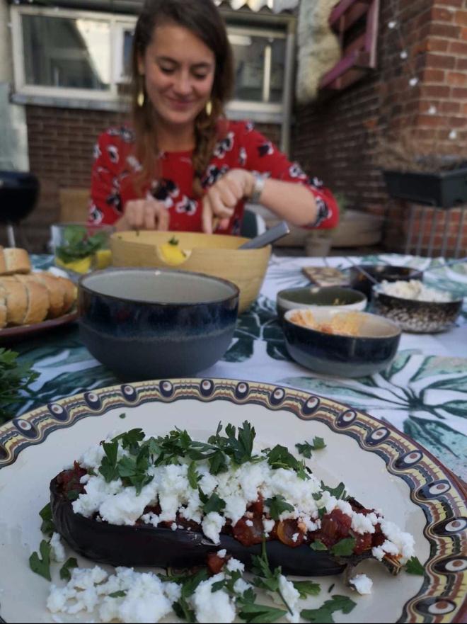 Foto van gedekte tafel met gegrilde aubergines en Sara
