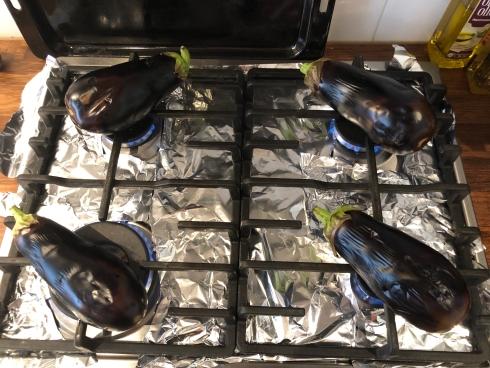 Foto van aubergines op gasfornuis om te roosteren