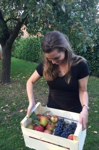 Sara met kist appels en druiven