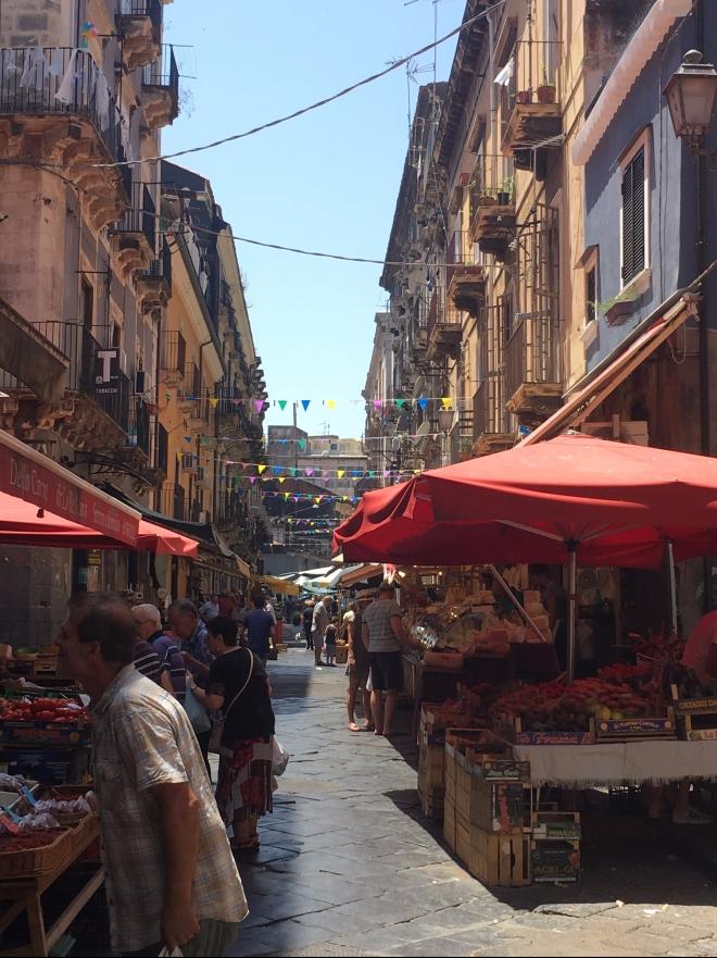 Foto van zonnige markt in Catania in straat met vlaggetjes