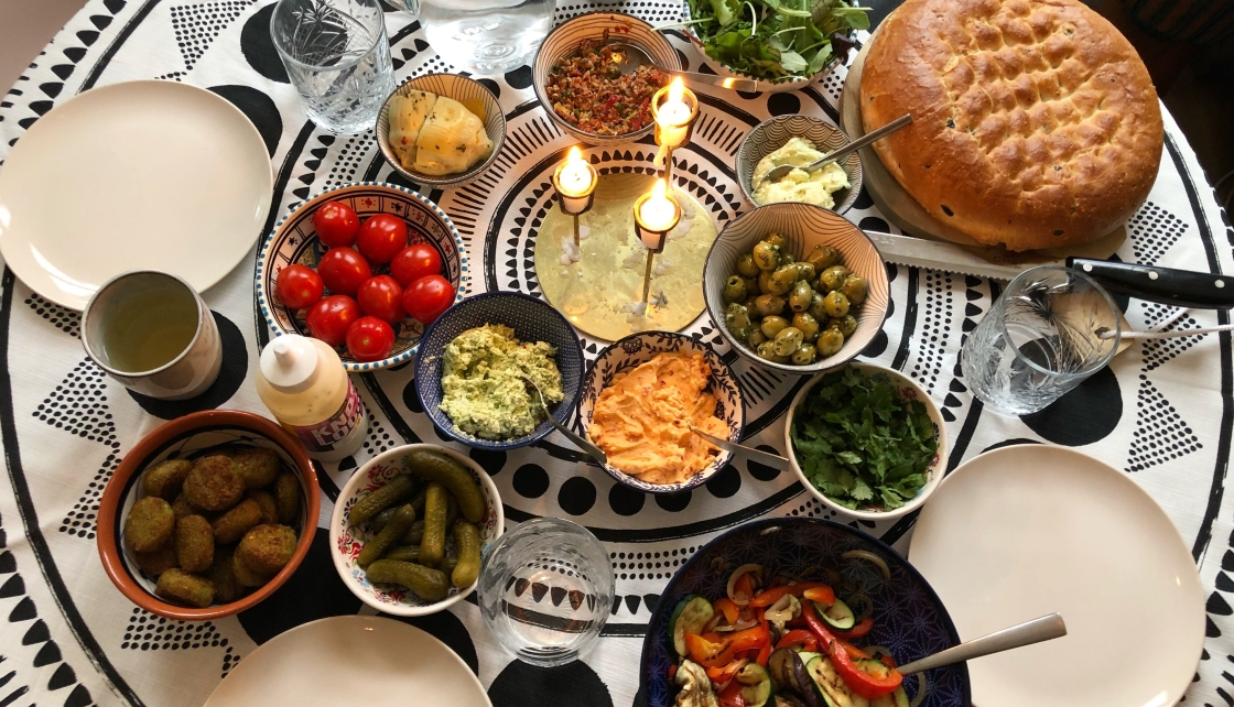 Foto van gedekte tafel met schaaltjes olijven, falafel en smeersels