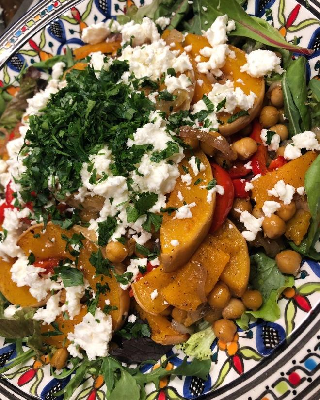 Foto van groente uit de oven, zoals pompoen, paprika, kikkererwten met feta en peterselie
