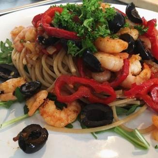 foto van spaghetti met garnalen en olijven