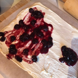 Foto van hoe jam over de creamcheese wordt uitgesmeerd op het deeg