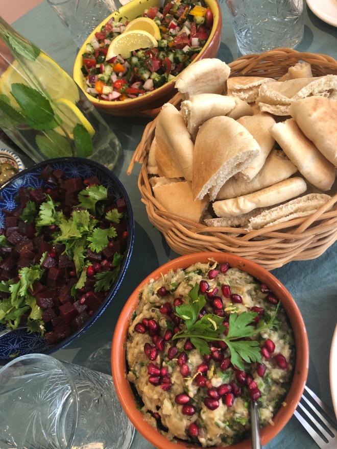 foto van schalen op tafel met pita's en baba ganoush