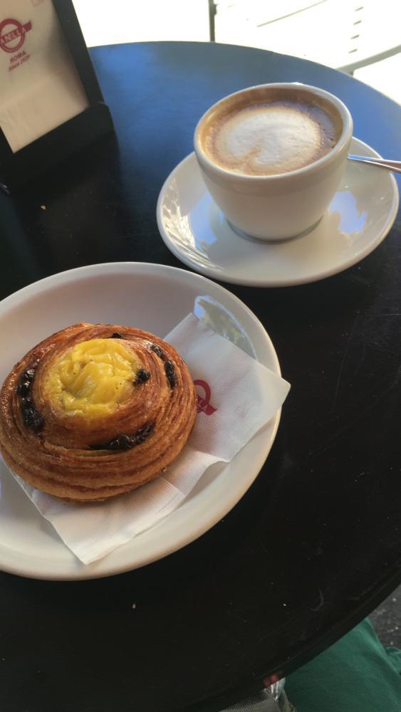 Foto van cappuccino en roombroodje op een terras