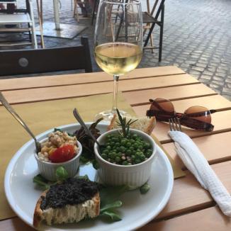 Foto van glas wijn en schaaltjes op terras
