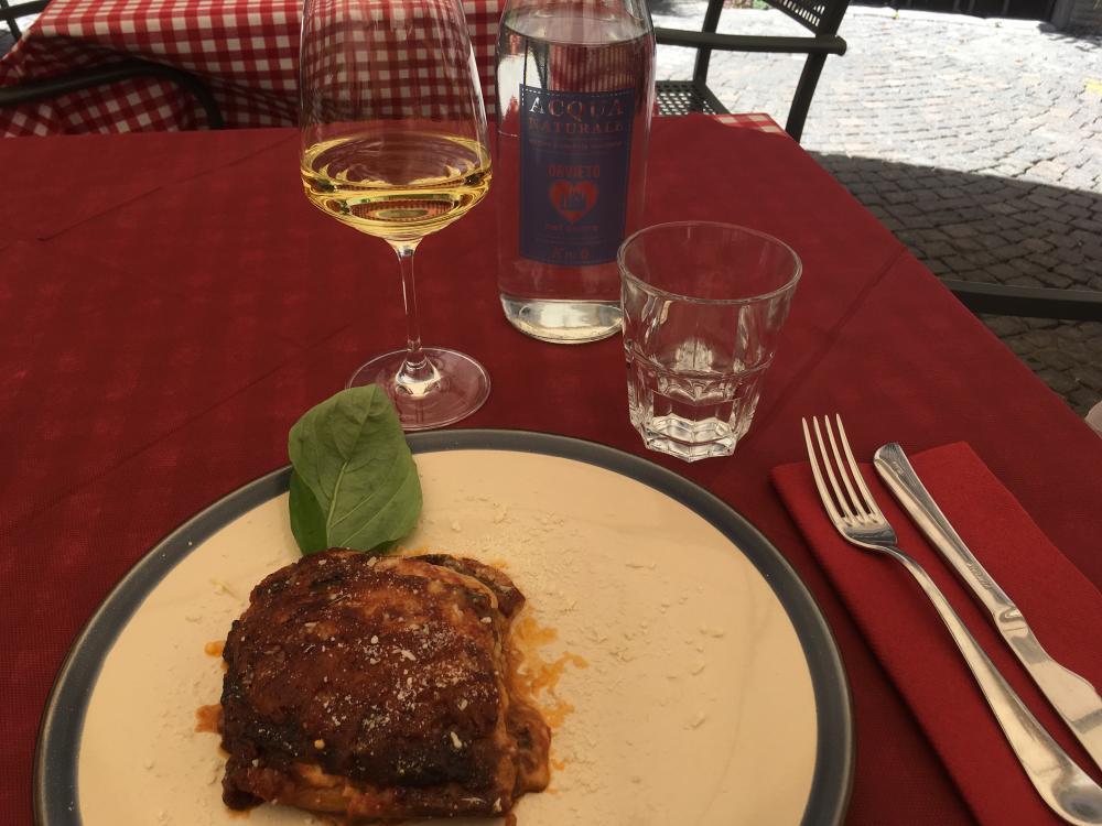 Foto van gedekte restauranttafel met melanzane en glas wijn