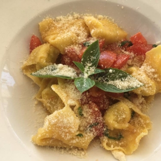 Foto van gevulde pasta met tomaten, basilicum en geraspte kaas