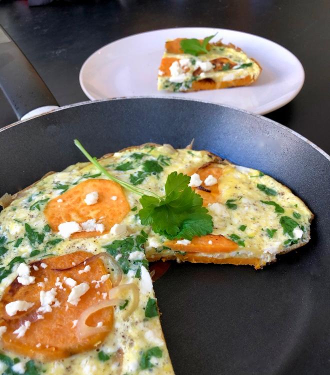 Foto van een pan met omelet met zoete aardappel, feta en peterselie