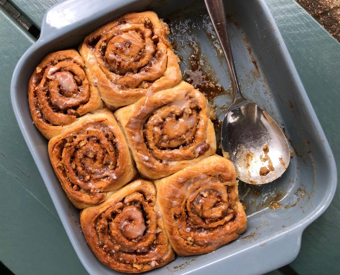 Foto van zes ronde broodjes in een schaal. Spiraal van kaneelsuiker in elk broodje.