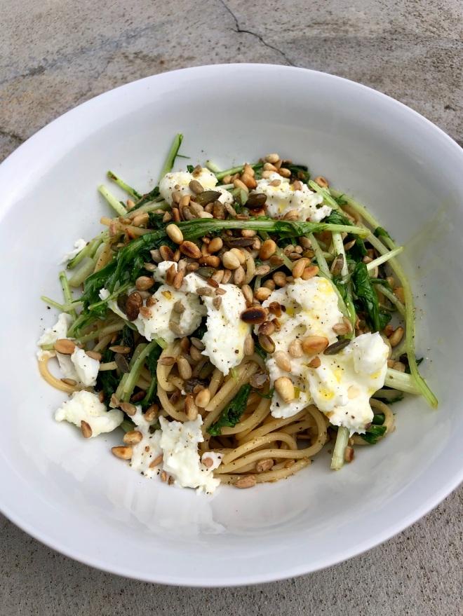 Foto van wit bord met spaghetti, groene raapstelen, mozzarella en nootjes